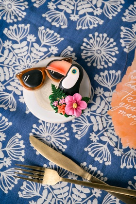 wedding reception styled shoot tropical theme blue linen gold flatware orange sunglass and toucan