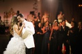 photo of bride in ostrich feather skirt wedding dress groom in white tuxedo jacket first dance