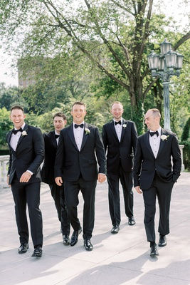 wedding portrait of groom and groomsmen in tuxedos walking at venue cleveland museum of art outdoor