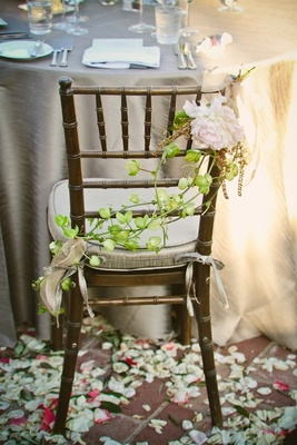 Bride and groom chairs wrapped in vines and flowers