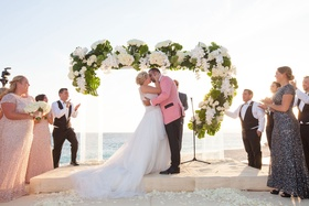 Lucite ceremony arch with split leaves, white orchids, ivory roses, green hydrangeas