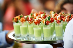 Green soup in shot glass with tomato and mozzarella skewer