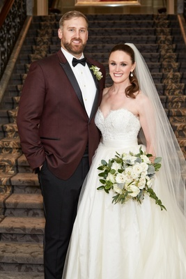 Bride in strapless ball gown detachable skirt sweetheart neckline groom in burgundy tuxedo bow tie