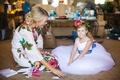 bride flower girl white dress flower crown blue accents leaves smiling before wedding