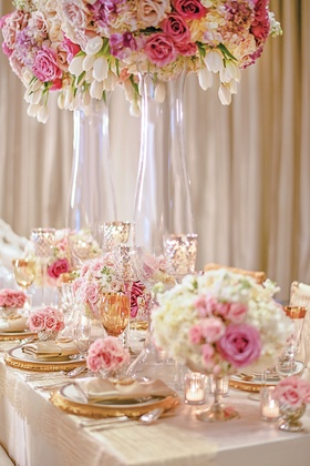 Styled shoot table with pink and white flowers and gold plates