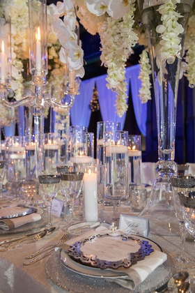 Wedding reception tall centerpiece white orchids floating candles silver plates chargers