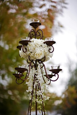 wrought iron candle stand with small votives and white flowers