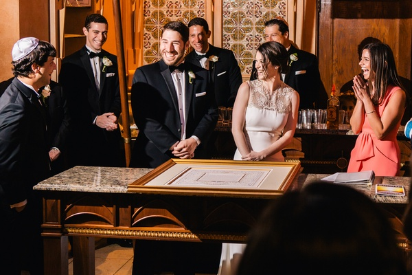 bride and groom sign ketubah at Jewish wedding ceremony bride in Lela Rose