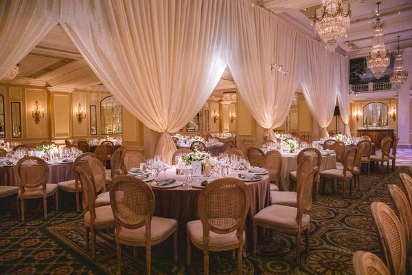 wedding reception drapery ballroom oval back wood chairs low centerpiece chandelier