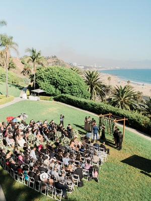 wedding ceremony on grass lawn bel air bay club wood arbor beach view pacific ocean