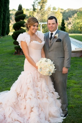 Bride in Mark Zunino blush ruffle dress and groom in grey suit and converse sneakers