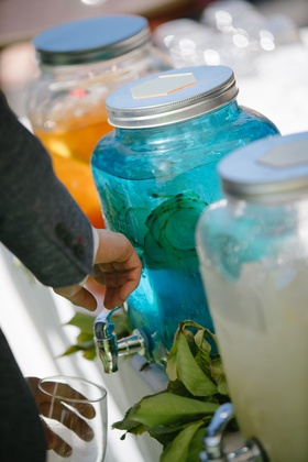 guest takes cucumber-infused water from blue container