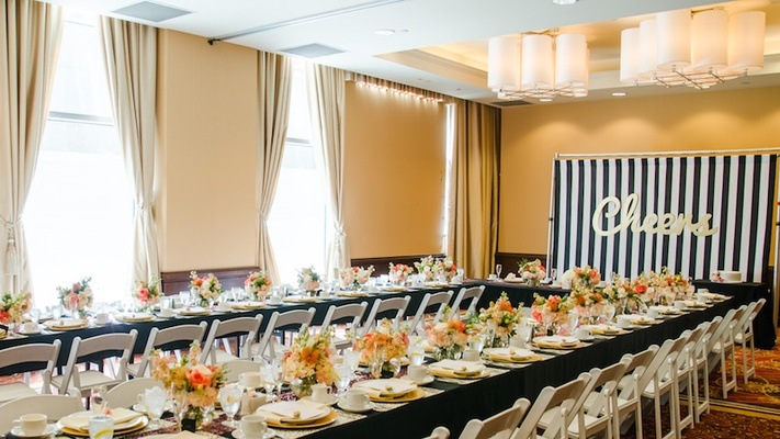 Wedding shower with black tablecloths, white chairs and white, pink, and orange flowers