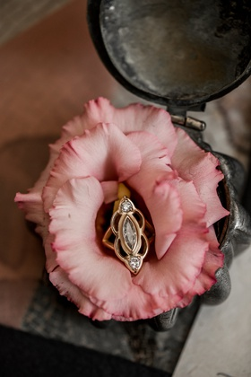 vintage-inspired engagement ring yellow gold marquise diamond and two round diamonds in pink rose