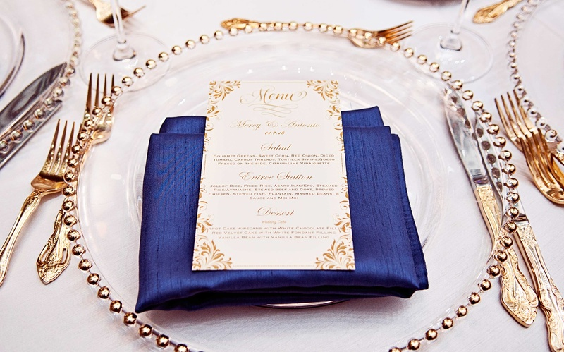 White tablecloth, gold flatware, gold menu card, navy blue dinner napkin, gold beaded charger plate