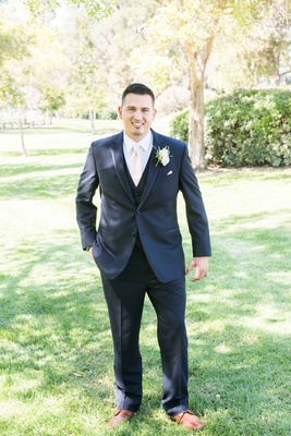 groom posing navy suit pink tie white boutonniere outside smiling before catholic ceremony