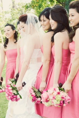 Pink bridesmaid dresses and bouquets of pink roses