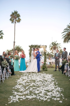 newlywed couple kiss at beach wedding with palm trees in back