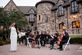Wedding ceremony on lawn of private estate backyard singer in white dress and musicians in chairs