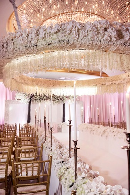 opulent wedding ceremony tall taper candles gold chairs white flowers orchid chandelier overhead