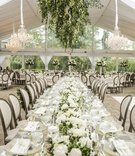 long mirror top table floral fixture above wicker runner modern tented reception wedding garden