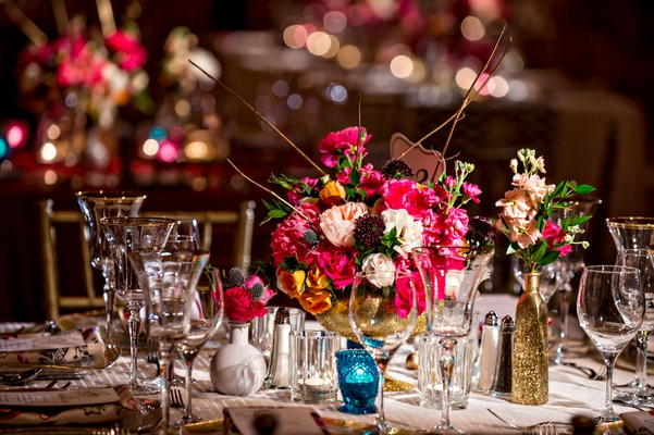 Flower arrangement at wedding reception with gold branches, pink, orange, and white flowers
