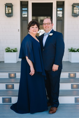 groom with glasses in navy suit and fun bow tie