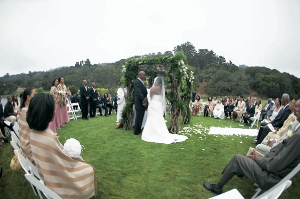 Outdoor ceremony on grass with guests surrounding the chuppah