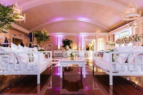 Wood floor ballroom at wedding reception white lounge furniture daybed couch white coffee table