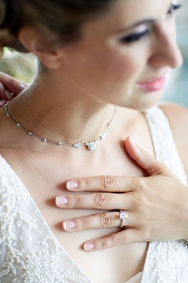 Bride with emerald cut pave diamond engagement ring and flower family heirloom necklace