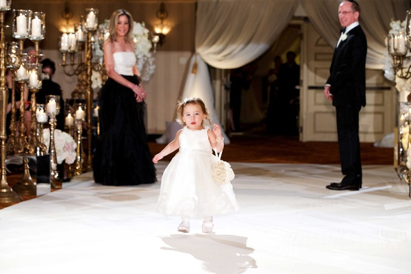 Flower girl in white dress, tights, and shoes, walking down aisle with flower pomander on wrist