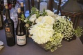 Bar at outdoor wedding reception with wood boxes of large and small white flowers and lanterns