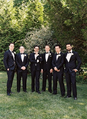 Men in tuxedos and bow ties standing on grass