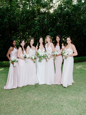 bride in crepe wedding dress with bridesmaids in light pink dresses of their choosing