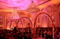 Ballroom wedding ceremony with chandeliers and pink lighting