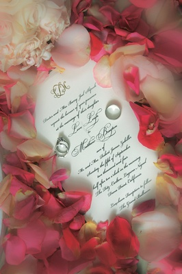 Wedding invitation surrounded by pink rose petals