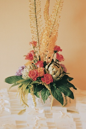 White table cards with bows below towering flower arrangement