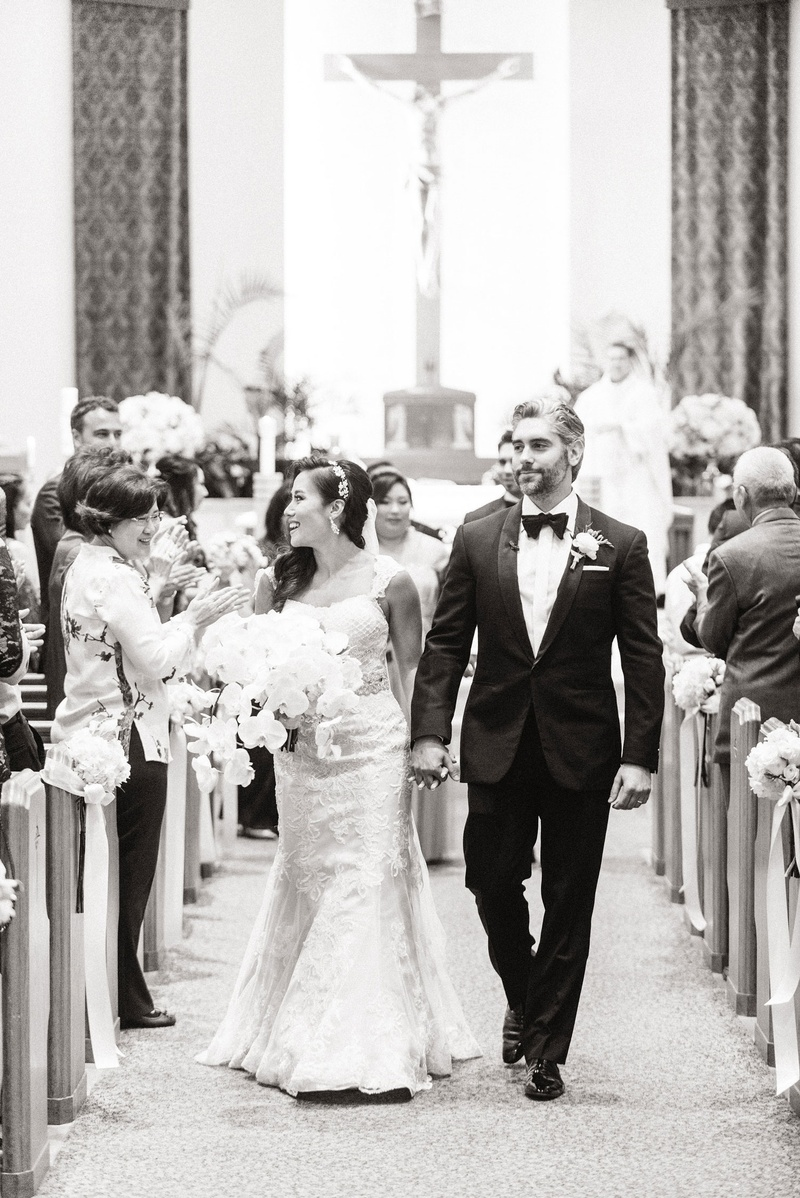 Black and white photo of bride and groom holding hands leaving the altar newlyweds