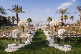 Grass lawn wedding ceremony white flower petals tall white flower arrangements gold chairs palm tree