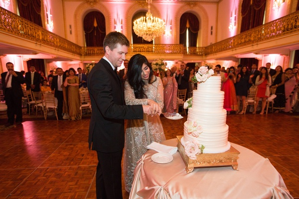 bride in elan, groom in armani, newlyweds cut cake