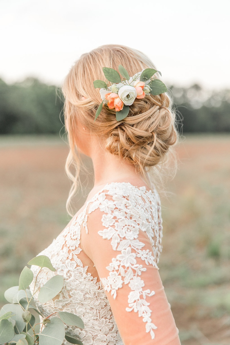 Bride in lace illusion long sleeve wedding dress with low updo and flower leaf floral hair clip