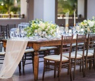 wedding reception long wood table with wood chairs fabric runner sheer gold taper candles yellow