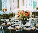 Table with gold chargers and black urn filled with orange, green, and pink flowers