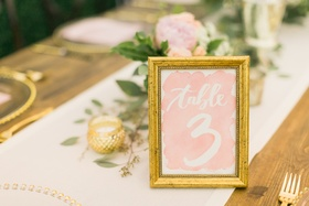 gold frame on watercolor table number with blush background