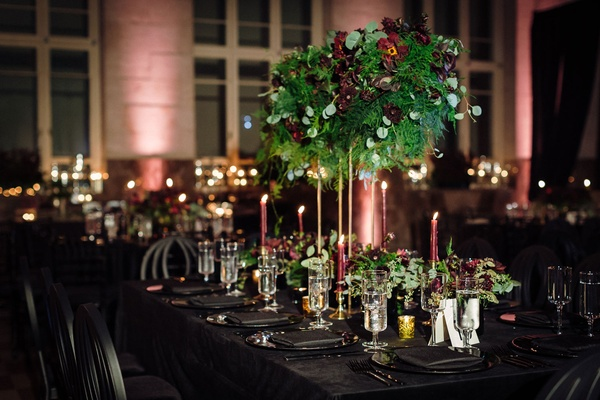 Reception with dark velvet linens, black charger, black napkin, black chair, tall centerpiece
