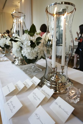 Seating card table with crystal glass vases and white flowers