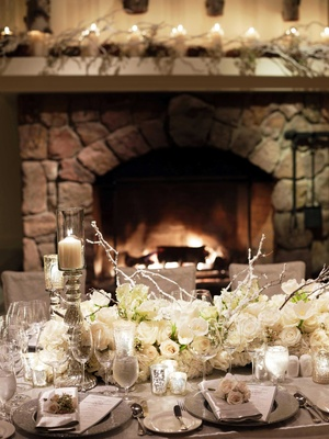 Winter wedding ideas for reception at indoor venue with fireplace and branch centerpieces
