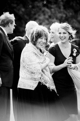 Black & white photo of smiling mother of the bride and sister of the bride in wraps on a windy day