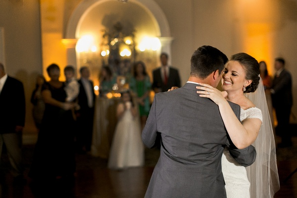 Bride in an off-the-shoulder Sottero and Midgley lace dress, veil dances with groom in grey suit