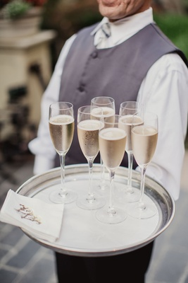 Server in grey vest and bow tie holding champagne flutes and monogram napkins on silver tray